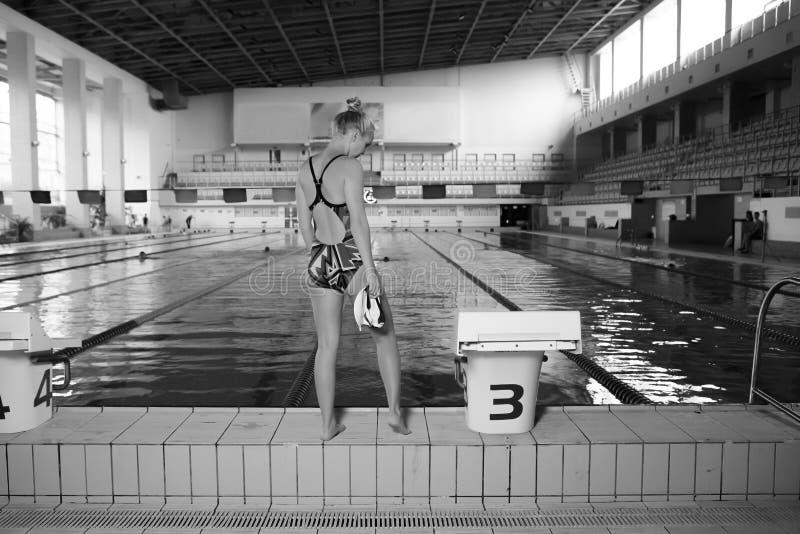 站立在水池前面的运动妇女 免版税库存照片