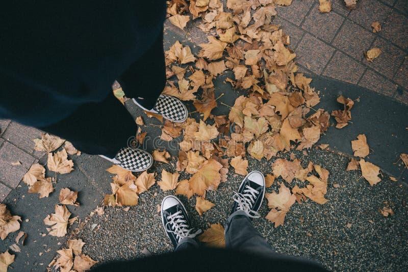 站立在水泥的落叶的两双人佩带的运动鞋的脚 免版税库存图片