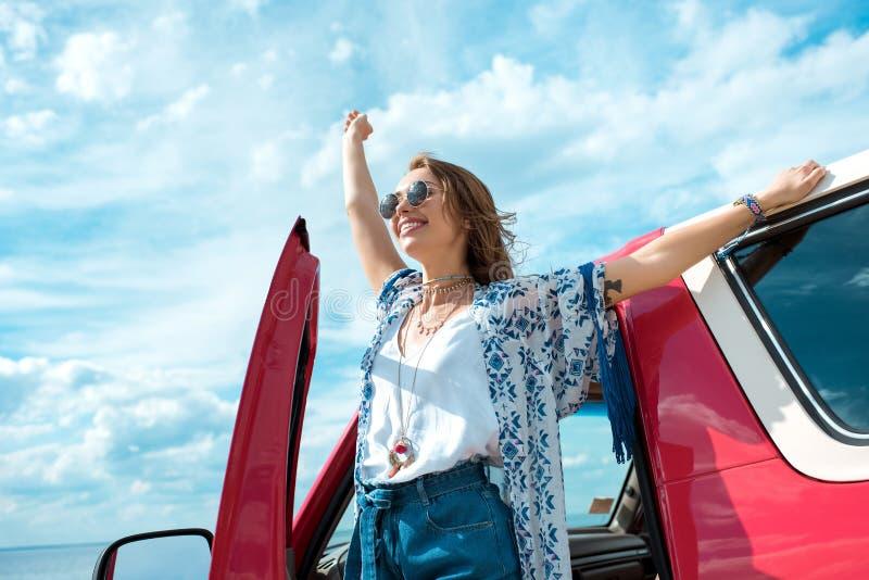 站立在汽车附近的太阳镜的激动的年轻女人 免版税库存图片