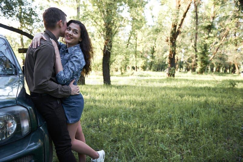 站立在汽车附近的夫妇在森林、浪漫感觉和爱里 免版税图库摄影