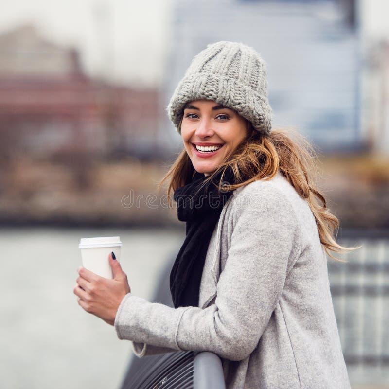 从站立在河堤防和享受的纸杯的微笑的妇女饮用的咖啡看法 免版税库存图片
