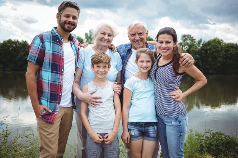 站立在河附近的愉快的多代的家庭 免版税库存照片