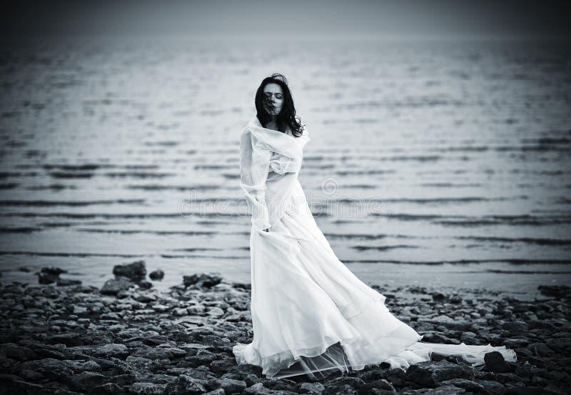 站立在沿海的白色礼服的美丽的哀伤的女孩 库存照片