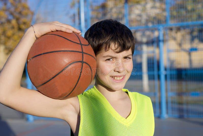 站立在法院的年轻蓝球运动员佩带黄色s 库存图片