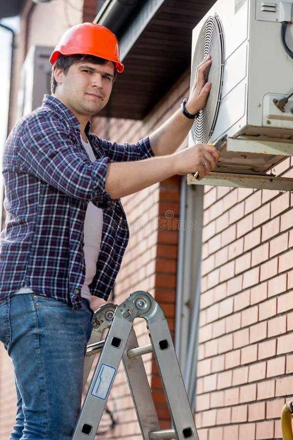 站立在活梯和修理空调器的男性安装工画象 库存照片
