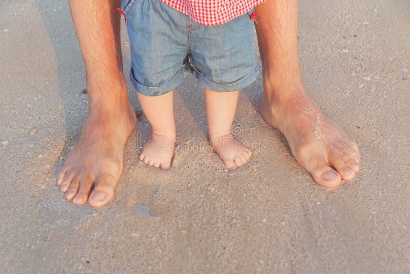 站立在浅水区的人和婴孩脚等待波浪 赤脚生和他的小女儿或儿子 免版税库存照片