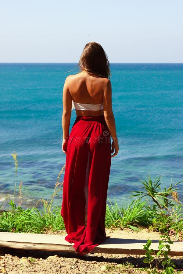 站立在海上的红色裙子的女孩 库存照片