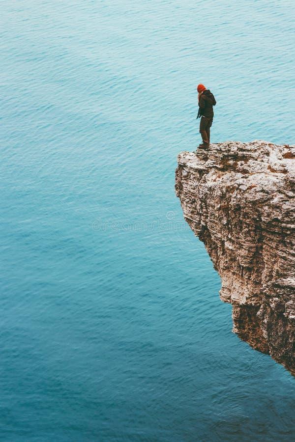 站立在海单独旅行生活方式概念冒险上的峭壁边缘的旅客 库存图片