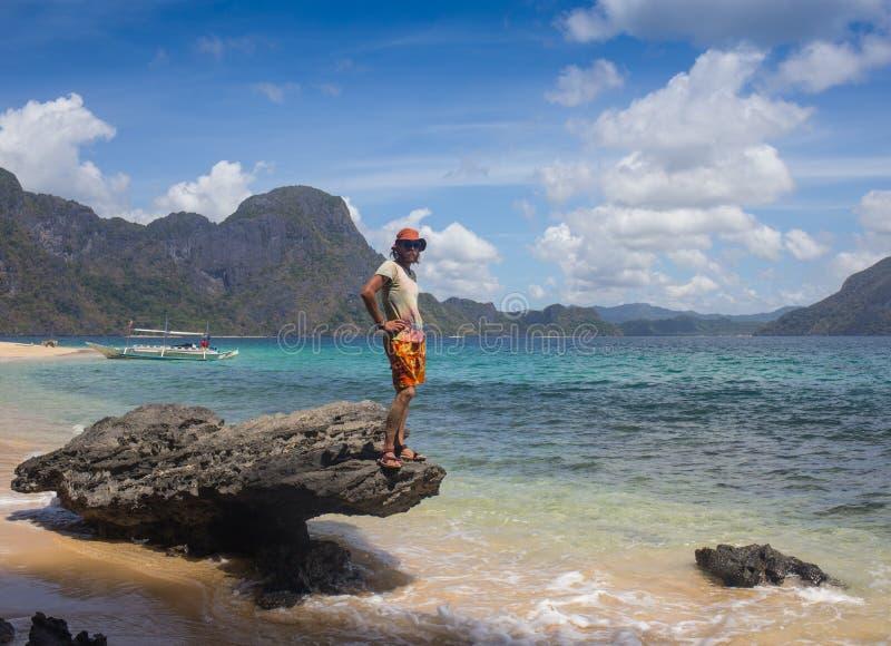 站立在海岸线和享用的年轻人 图库摄影