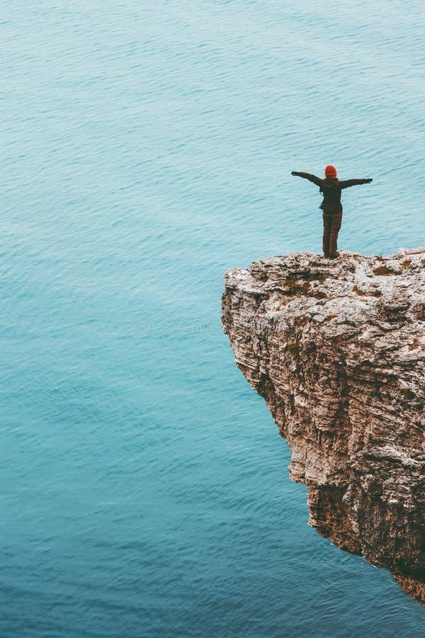 站立在海手被上升的旅行生活方式成功刺激概念上的峭壁的愉快的旅客 免版税库存照片