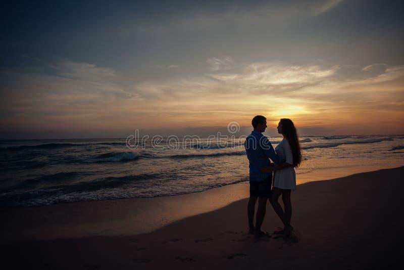 站立在海滩和互相看在日落背景的两个年轻恋人 Sillhouette夫妇爱 免版税库存照片