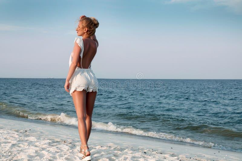 站立在海滩和看对海的夏天礼服的女孩 免版税库存照片