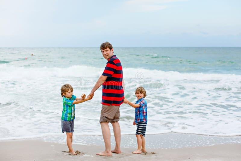 站立在海滩海洋和看在天际的两个愉快的小孩男孩和父亲在风暴日 家庭,爸爸 免版税库存照片