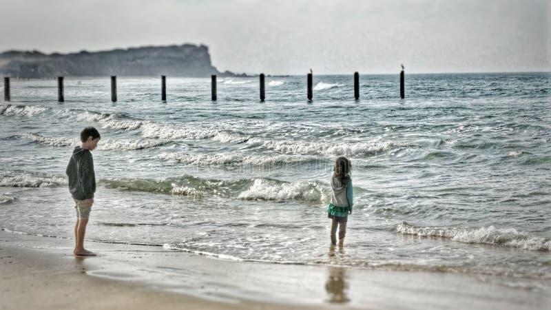 站立在海滩的两个幼儿观看波浪 免版税库存照片