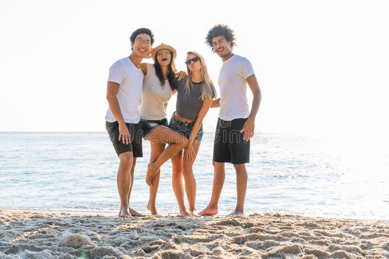 站立在海滩的激动的年轻朋友画象  享受一天的多种族小组朋友在海滩 免版税库存照片
