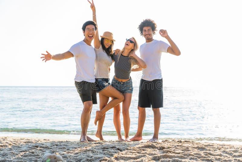 站立在海滩的激动的年轻朋友画象  享受一天的多种族小组朋友在海滩 免版税库存图片