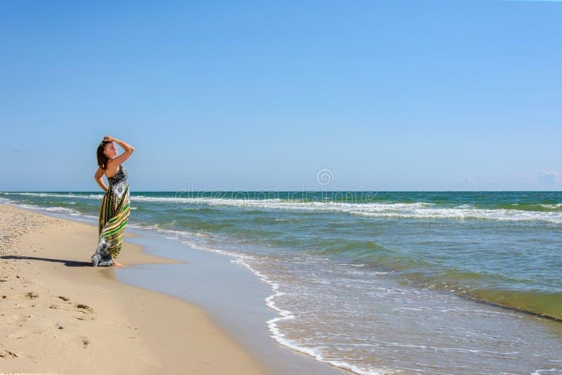 站立在海滩的美丽的女孩太阳镜和礼服的黑海 免版税库存图片