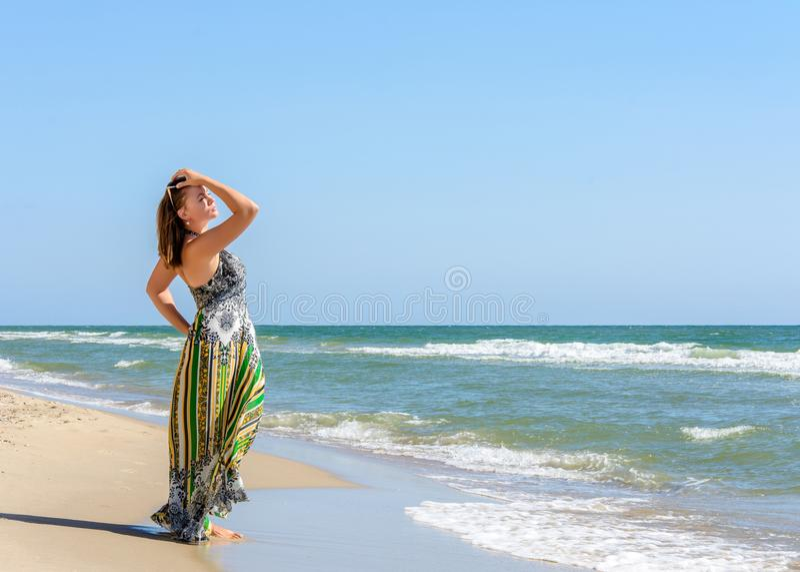 站立在海滩的美丽的女孩太阳镜和礼服的黑海 库存图片
