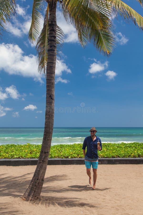 站立在海滩的英俊的微笑的人 免版税图库摄影