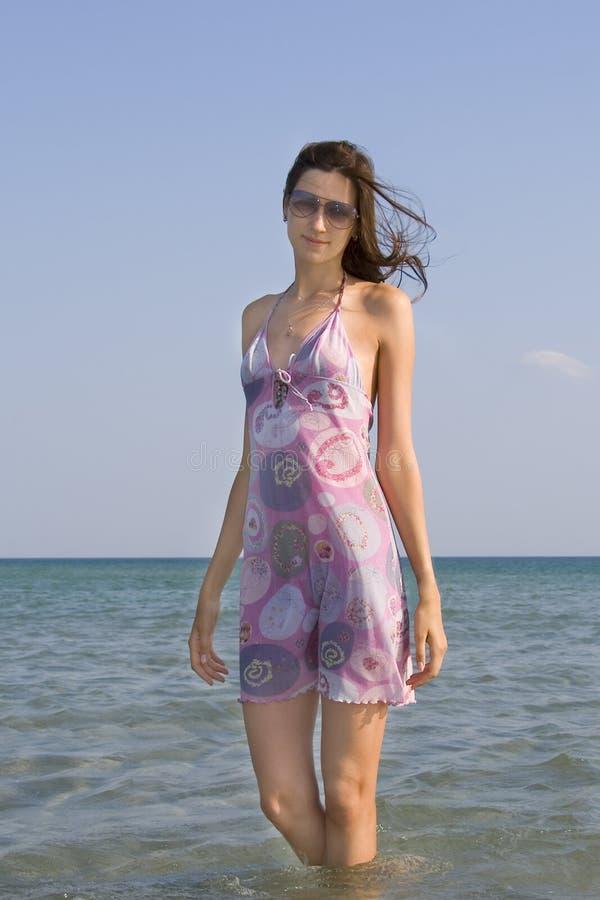 站立在海的太阳镜的少女 免版税图库摄影