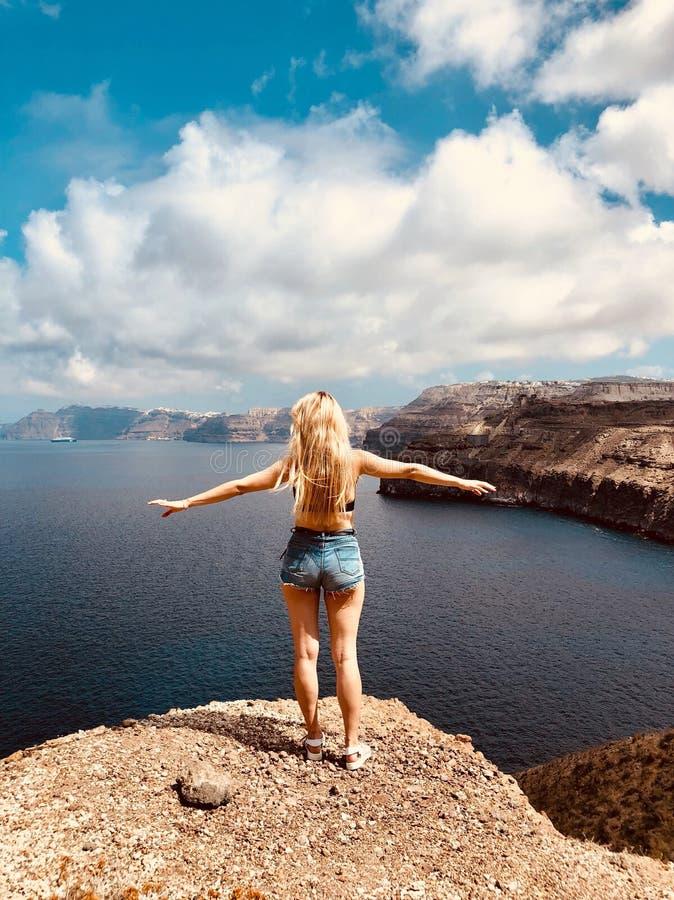 站立在海的女孩晃动,享受自由,感觉女性尊严 图库摄影
