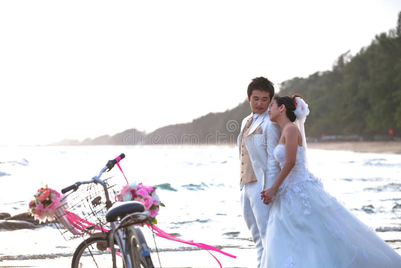 站立在海的新郎和新娘在老经典自行车旁边靠岸 免版税图库摄影
