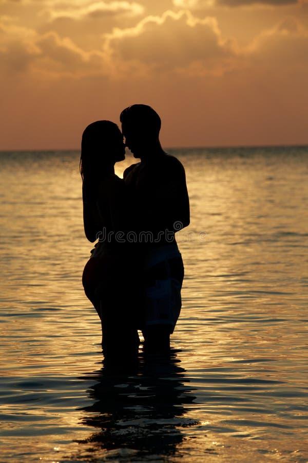 站立在海的浪漫夫妇剪影  免版税图库摄影