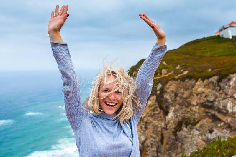 站立在海角Roca,辛特拉,葡萄牙的愉快的女性游人 免版税库存照片