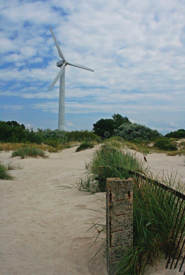 站立在海边的被放弃的风轮机的明亮的图片围拢由灌木和沙子 库存图片