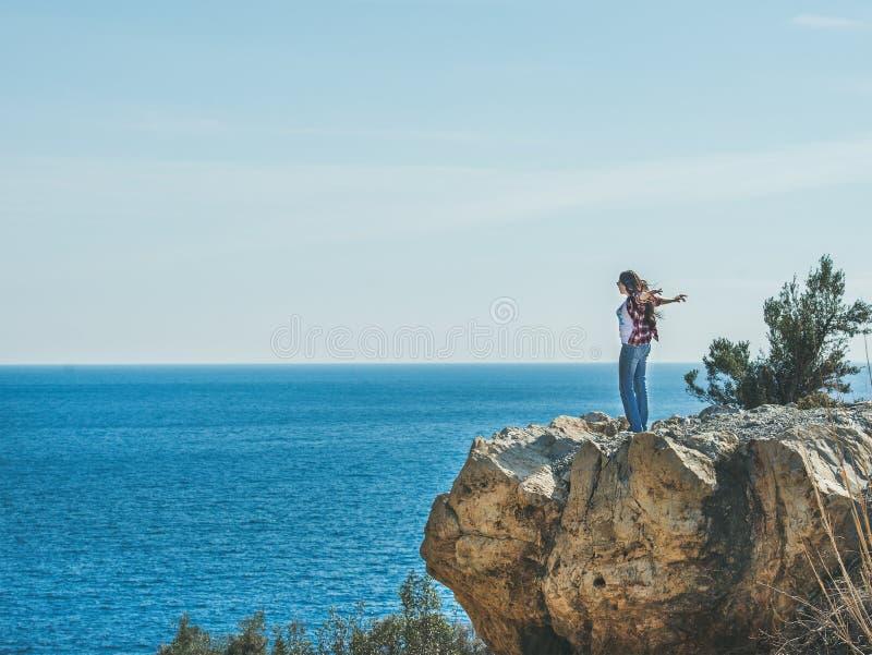 站立在海,土耳其的岩石的年轻愉快的女孩旅客 免版税库存图片