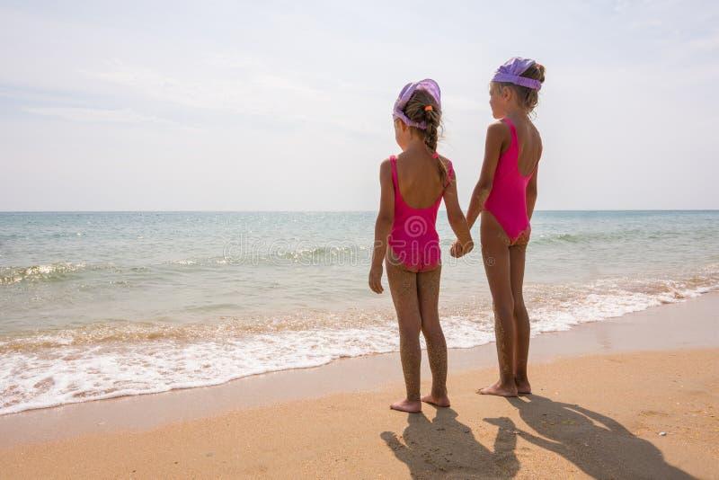 站立在海滩和神色的游泳衣的两个女孩在天际 图库摄影