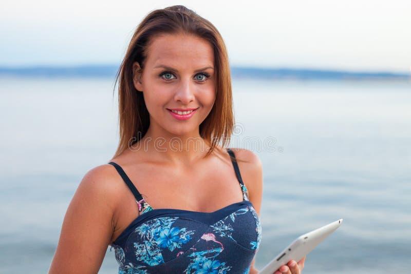 站立在海滩和采取片剂的美丽的妇女 库存照片