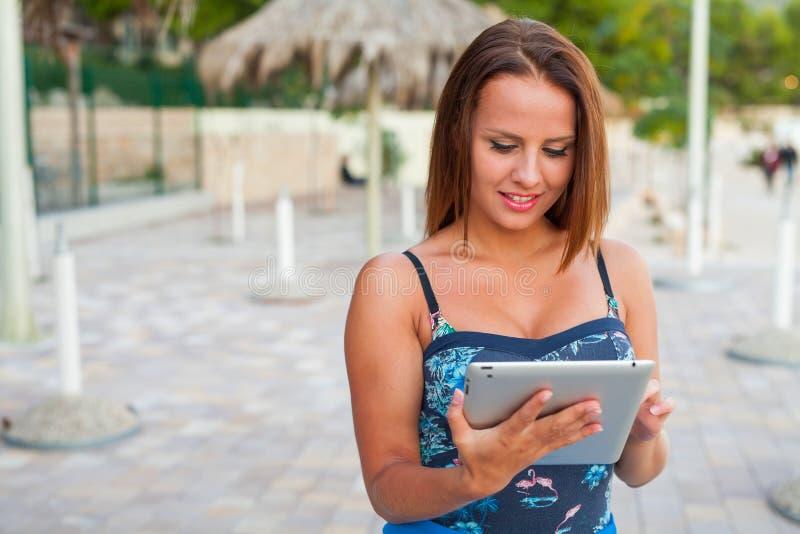 站立在海滩和采取片剂的美丽的妇女 免版税库存图片