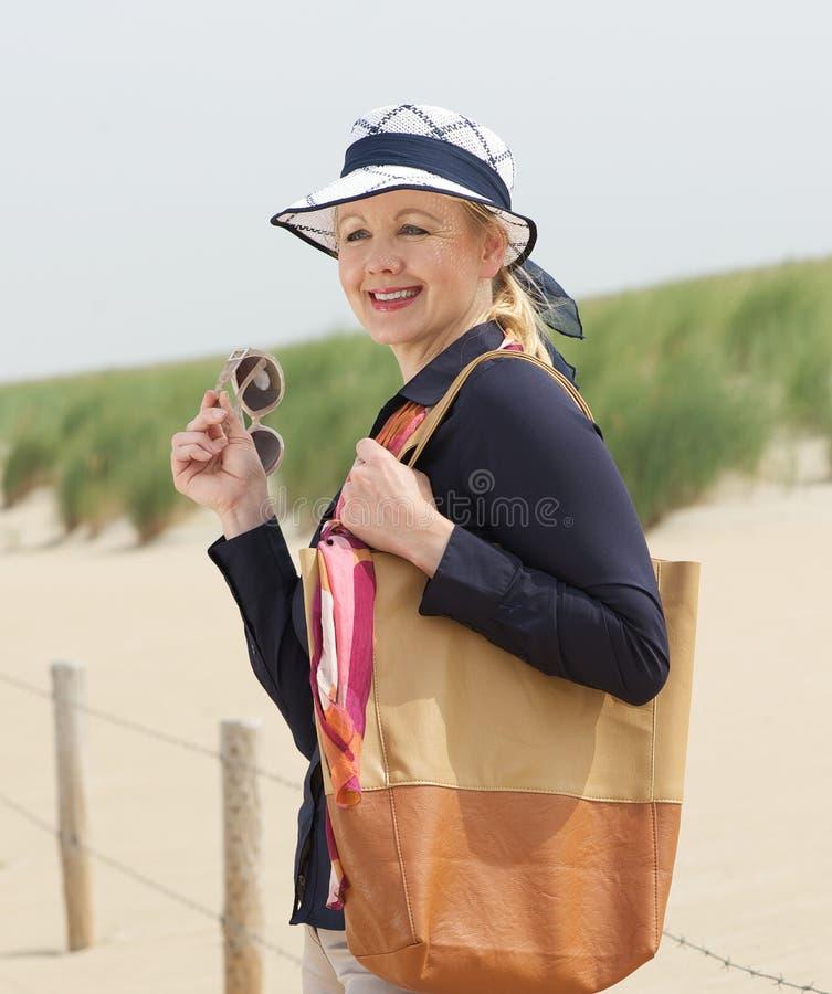 站立在海滩的一个可爱的老妇人的画象 免版税库存照片