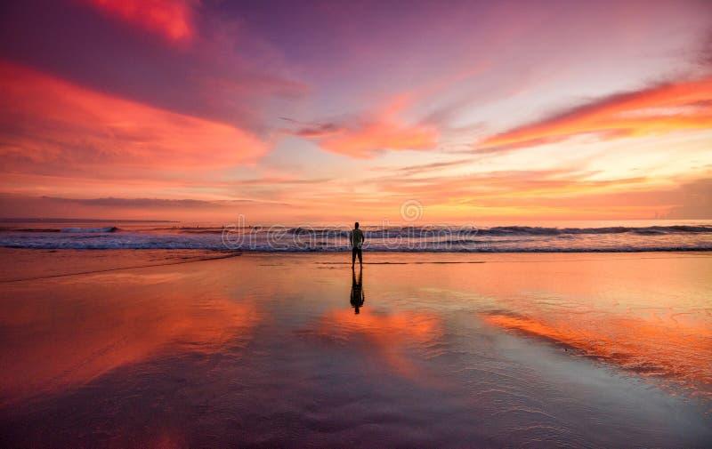 站立在海滩的一个孤立人在日落 免版税库存照片