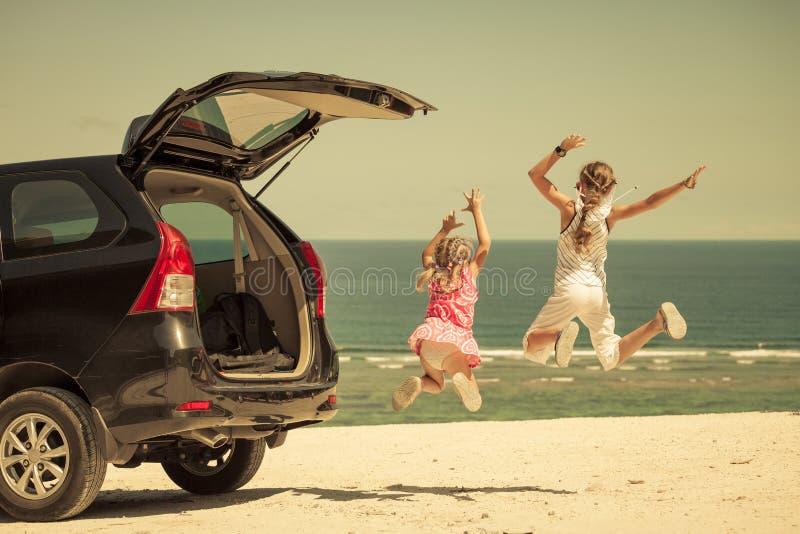 站立在海滩的一辆汽车附近的两个姐妹 免版税库存照片