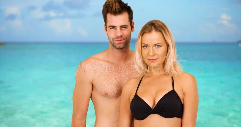 站立在海滩的性感的白色千福年的夫妇画象  免版税库存图片