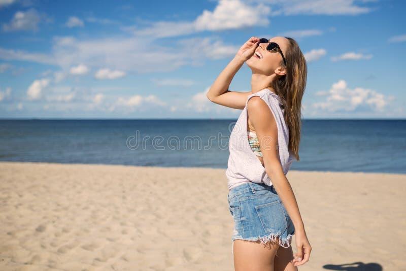 站立在海滩的愉快的少妇查寻 免版税库存图片