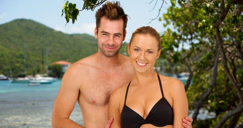 站立在海滩的有吸引力的千福年的夫妇微笑,当在巡航时 图库摄影