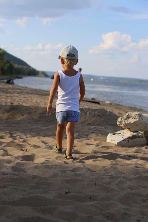 站立在海滩的沙子的小男孩在河附近 免版税图库摄影