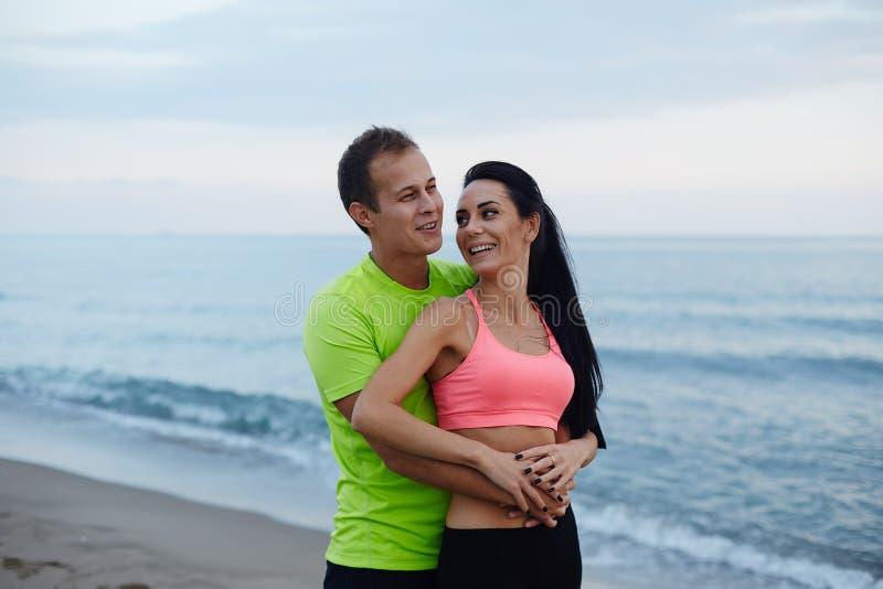 站立在海滩的浪漫夫妇享受美好的晚上 免版税库存图片