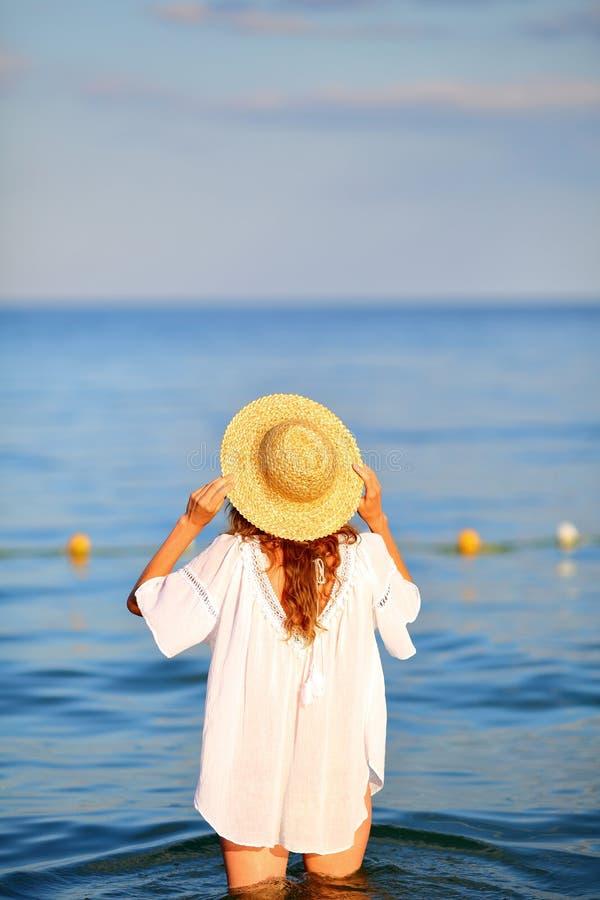 站立在海滩的海水的草帽的妇女 库存照片