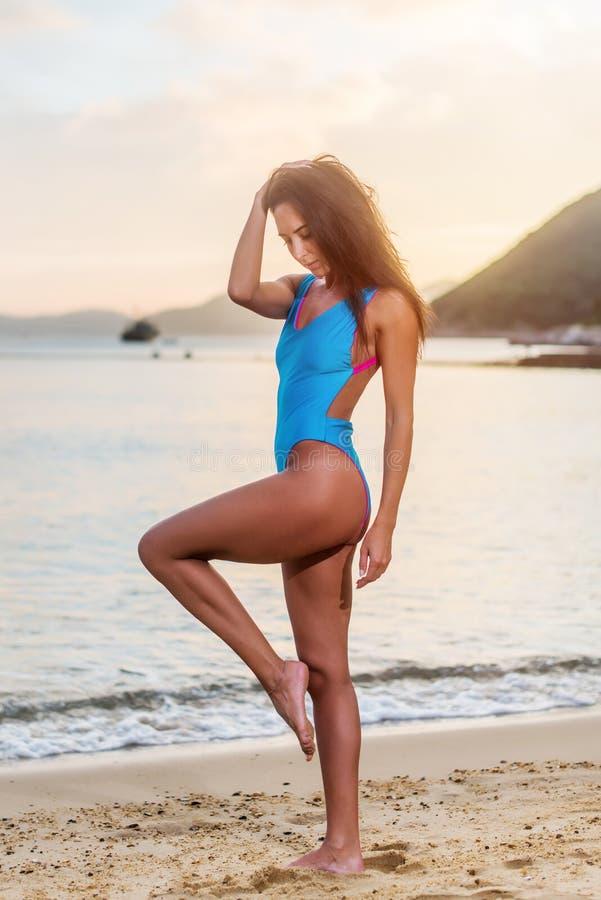 站立在海滨的游泳衣的可爱的被晒黑的女性游人在海滨胜地 免版税库存图片