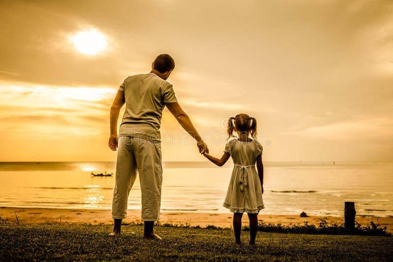 站立在海滩的父亲和女儿 库存照片
