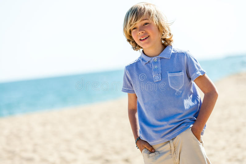 站立在海滩的英俊的男孩画象。 免版税库存照片