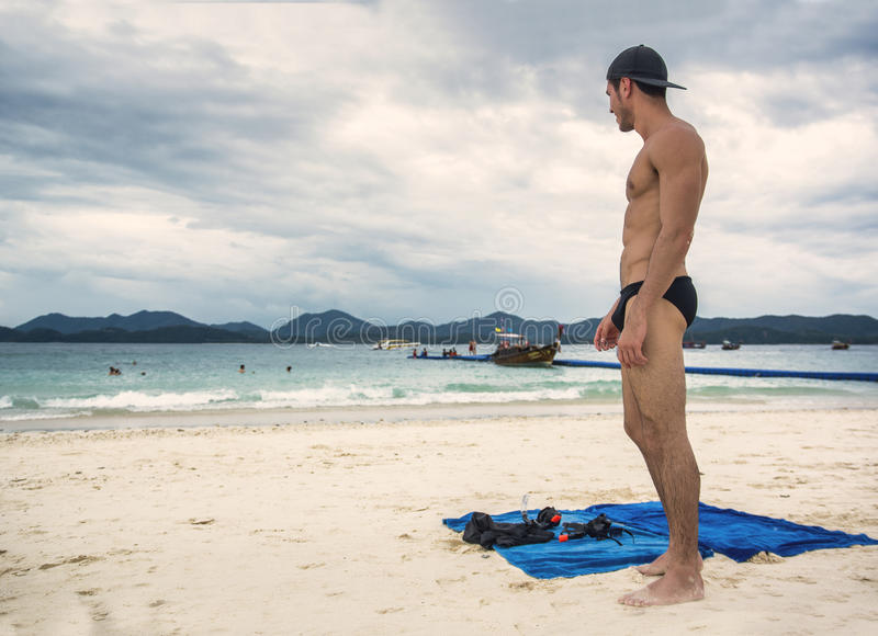 站立在海洋的边缘的年轻人 免版税库存照片