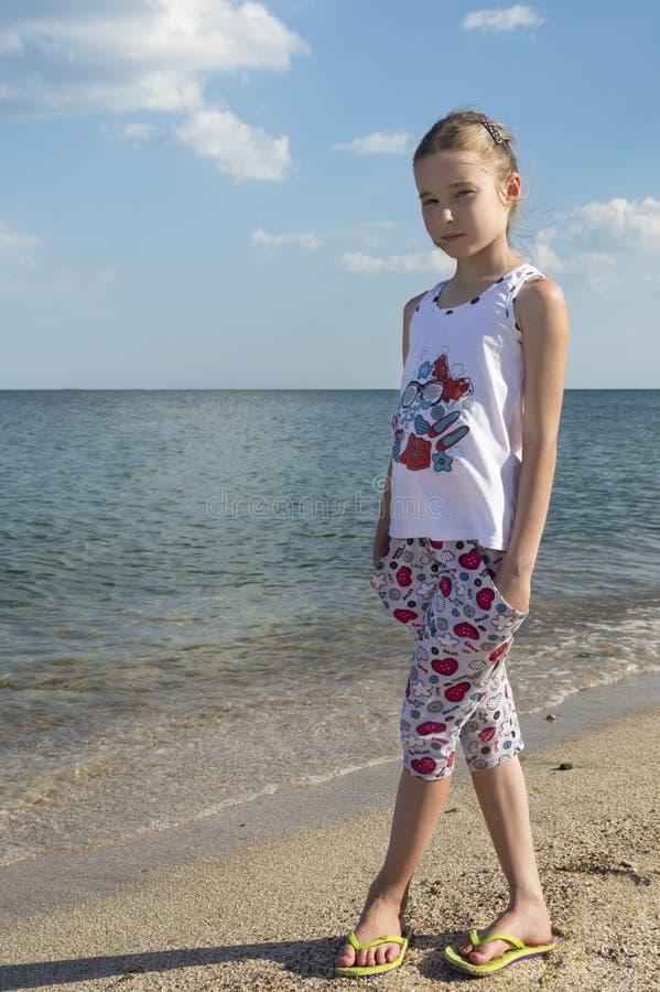 站立在海滨的年轻俏丽的女孩 免版税库存照片