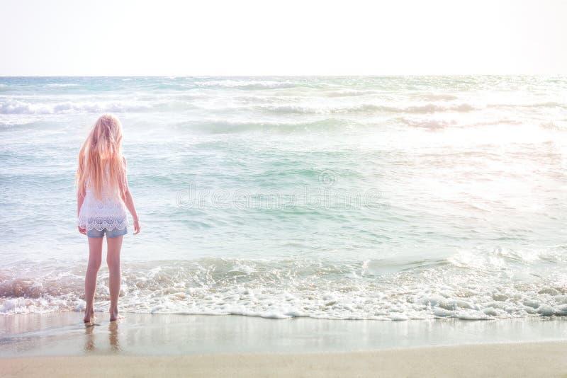 站立在海滩的年轻白肤金发的女孩 免版税库存图片