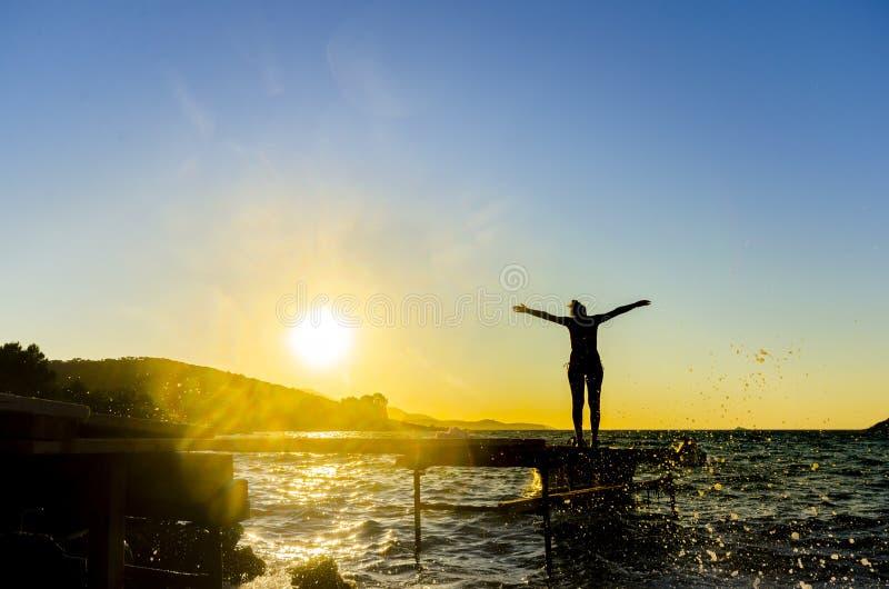 站立在海滩码头的健康年轻西班牙妇女画象用她的手伸出反对日落 免版税库存照片