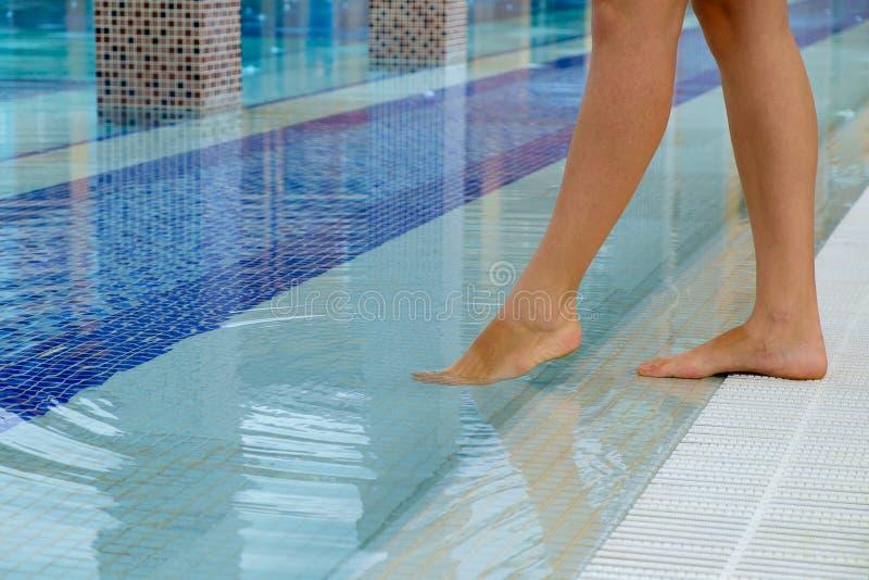 站立在游泳池和品尝边缘的少妇腿浸洗她的在它的水的温度腿的,在su 库存图片